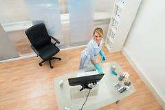 Jong meisje schoonmakend bureau stock afbeeldingen
