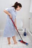 Jong meisje schoonmakend toilet royalty-vrije stock afbeeldingen