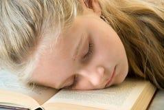 Jong meisje in slaap in een boek Stock Afbeeldingen