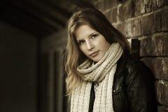 Jong meisje tegen een bakstenen muur Stock Afbeeldingen