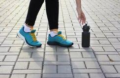Jong meisje in tennisschoenen die voor een fles bereiken Stock Afbeelding