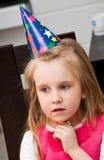 Jong meisje in verjaardagshoed Stock Afbeelding