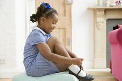 Jong meisje vooraan gang het bevestigen schoen en smilin Royalty-vrije Stock Afbeeldingen