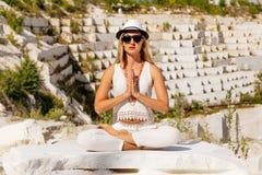 Jong meisje in witte kledingszitting in Lotus-positie, Padmasana inzake de achtergrond van de witte marmeren steengroeve Stock Afbeelding