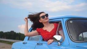 Jong meisje in zonnebril die uit uitstekend autoraam leunen en van reis genieten De vrouw kijkt uit van het bewegen van retro aut stock videobeelden