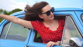 Jong meisje in zonnebril die uit uitstekend autoraam leunen en van reis genieten De vrouw kijkt uit van het bewegen van retro aut stock footage