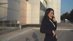 Jong meisje in zwart kostuum die op smartphone tegen de achtergrond spreken van bureaucentrum openlucht stock video