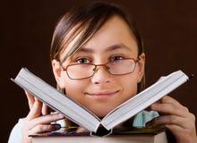 Jong meisjesgezicht met een open boek Stock Afbeeldingen