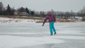 Jong meisjesijs die op bevroren meer schaatsen stock footage