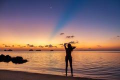 Jong meisjesverblijf op het strand en het letten van de op zonsondergang Royalty-vrije Stock Foto
