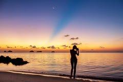 Jong meisjesverblijf op het strand en het letten van de op zonsondergang Royalty-vrije Stock Afbeeldingen