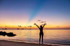 Jong meisjesverblijf op het strand en het letten van de op zonsondergang Royalty-vrije Stock Afbeelding