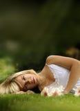 Jong model dat in gras bepaalt Stock Afbeeldingen