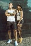 Jong modieus getatoeeerd paar die zich bij de betegelde zwarte muur op de straat bevinden royalty-vrije stock afbeelding