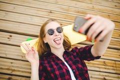 Jong modieus stedelijk meisje die in hipsteruitrusting selfie terwijl het liggen met op houten pijler maken royalty-vrije stock foto