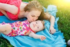 Jong moeder kussend meisje die op blauwe deken bij gazon liggen Stock Fotografie