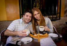 Jong mooi Amerikaans toeristenpaar die Spaanse typische ontbijt hete chocolade met churros gelukkig glimlachen hebben Stock Afbeeldingen