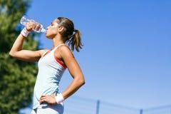 Jong mooi atleten drinkwater na het uitoefenen Stock Foto's
