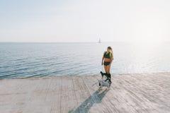 Jong mooi atletisch meisje met lang blond haar in zwarte kleren en twee van haar honden die sporten doen bij zonsopgang door het  Stock Foto's