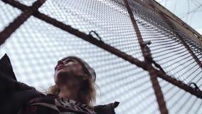 Jong mooi blondemeisje in de winterparka achter de omheining van de kettingsverbinding stock footage
