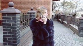 Jong mooi blondemeisje die op smartphone spreken stock video