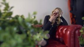 Jong mooi blondemeisje die stembericht op de telefoon op de rode laag maken De binnenlandse installaties zijn in de voorgrond stock video