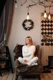 Jong mooi blondemeisje in een warme witte gebreide sweater op de achtergrond van een eenvoudige comfortabele ruimte met Kerstmis stock afbeelding
