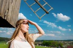 Jong mooi blondemeisje met lang haar op groen gebied in openlucht etnisch dorp Pirogovo stock afbeeldingen