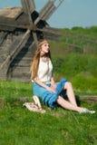 Jong mooi blondemeisje met lang haar op groen gebied in openlucht etnisch dorp Pirogovo stock foto