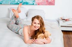 Jong mooi blondemeisje in pyjama's op het bed in zijn ruimte en h Royalty-vrije Stock Fotografie