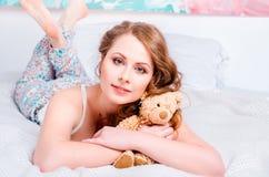 Jong mooi blondemeisje in pyjama's op het bed in zijn ruimte en h Royalty-vrije Stock Foto