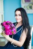 Jong mooi brunette in blauwe kleding met een boeket Stock Fotografie