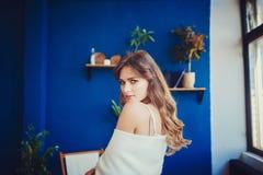Jong mooi brunette in gebreide kleren thuis royalty-vrije stock afbeelding