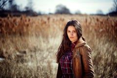 Jong mooi brunette met lange krullende haartribunes op een gebied Stock Foto's