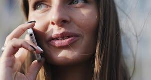 Jong mooi donkerbruin meisje met steunen op haar tanden die op mobiele telefoon spreken stock videobeelden