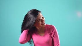 Jong mooi donkerbruin model die wat betreft haar op turkooise achtergrond glimlachen stock videobeelden
