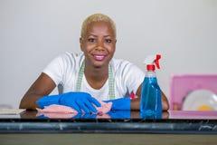 Jong mooi en gelukkig afro Amerikaans zwarte in was rubberkleren die huiskeuken met doek schoonmaken die vrolijke glimlachen royalty-vrije stock foto's