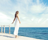 Jong, mooi en gezond meisje op houten pijler bij de zomer Vaca stock foto