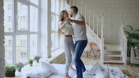 Jong mooi en houdend van paar die en op bed in de ochtend thuis dansen kussen stock video