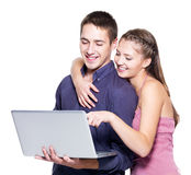 Jong mooi glimlachend paar dat laptop bekijkt Royalty-vrije Stock Foto's