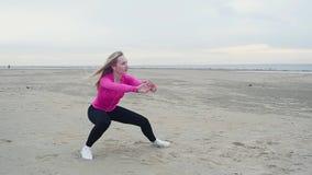 Jong mooi meisje belast met het uitrekken van spieren van benen op verlaten strand stock footage