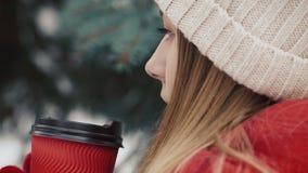 Jong mooi meisje binnen in warme kleren die zich dichtbij de Kerstbomen in sneeuw bevinden die hete drank van het document drinke stock videobeelden