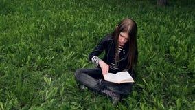 Jong mooi meisje dat een boek leest openlucht stock footage