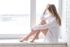 Jong mooi meisje in de witte zitting van het men'soverhemd op een vensterbank royalty-vrije stock afbeeldingen