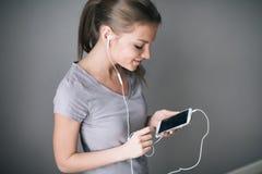 Jong mooi meisje die aan muziek met hoofdtelefoons luisteren terwijl het tonen van het lege scherm mobiele telefoon over grijs royalty-vrije stock afbeeldingen