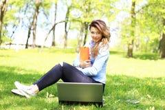 Jong mooi meisje die aan openlucht laptop werken, liggend op gras, Kaukasische 20 jaar oud royalty-vrije stock afbeeldingen