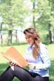 Jong mooi meisje die aan openlucht laptop werken, liggend op gras, Kaukasische 20 jaar oud stock afbeelding