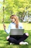 Jong mooi meisje die aan openlucht laptop werken, liggend op gras, Kaukasische 20 jaar oud royalty-vrije stock afbeelding