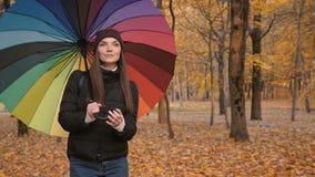 Jong mooi meisje die alleen in de herfstpark gaan met kleurenambrella 50fps stock video
