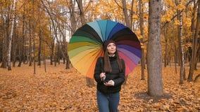 Jong mooi meisje die alleen in de herfstpark gaan met kleurenambrella 50fps stock footage
